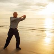 anciano-asiatico-mayor-practica-tai-chi-pose-yoga-amanecer-playa_1286-3006